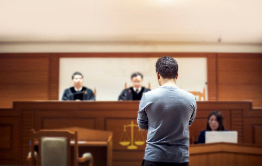 man standing inside a courtroom
