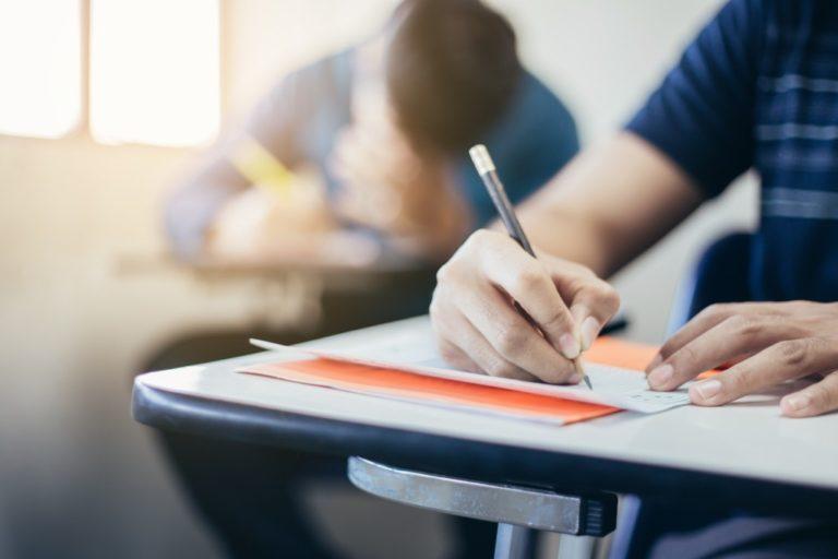 mature man writing during an exam