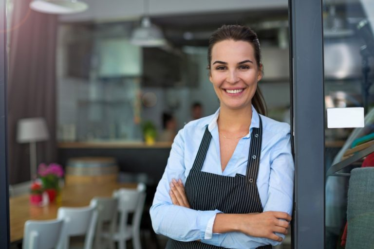 woman leaning against the door of her restaurant