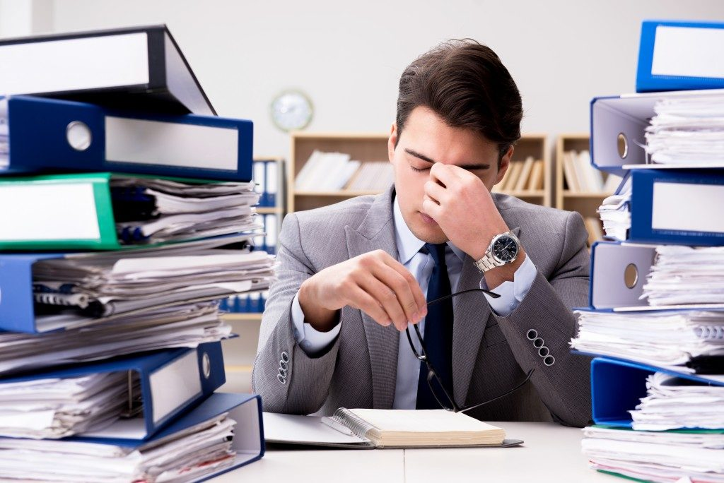 Employee under so much stress, piled up with papers