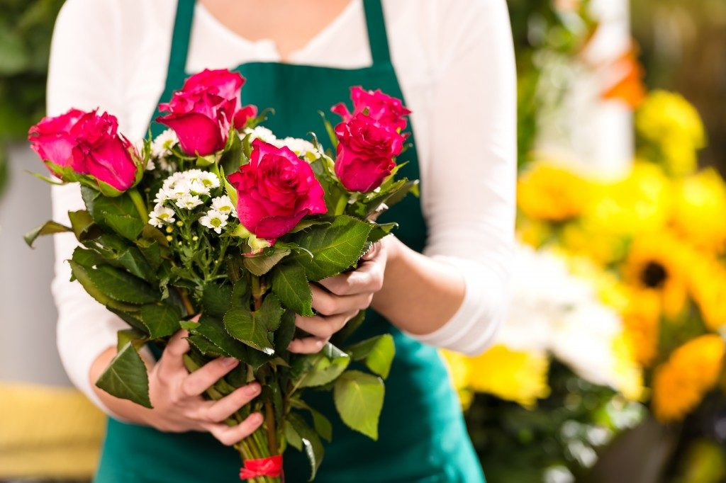 Florist hands showing red roses bouquet flowers shop market