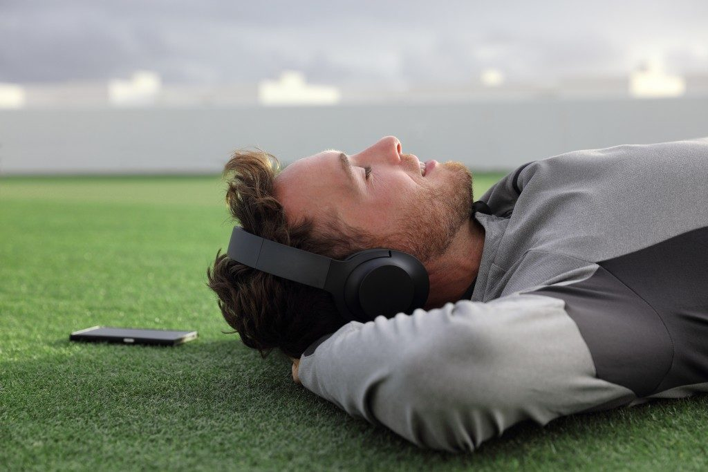 Man lying down on grass with headphones