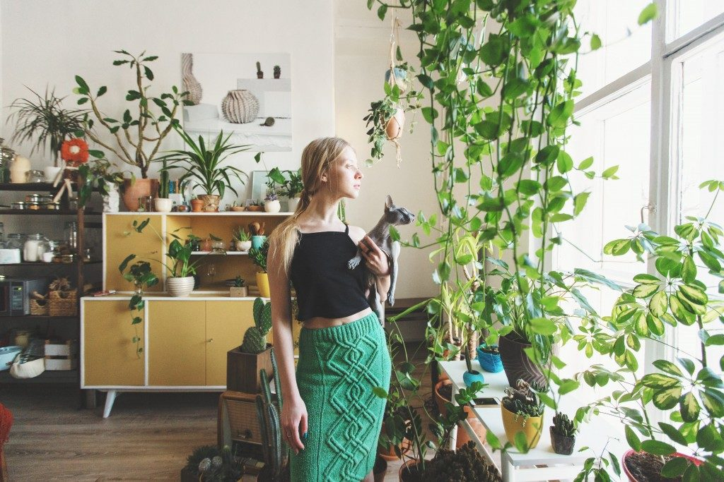 woman with plants in her living room