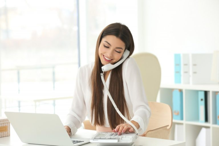 woman talking by telephone while working with laptop in office
