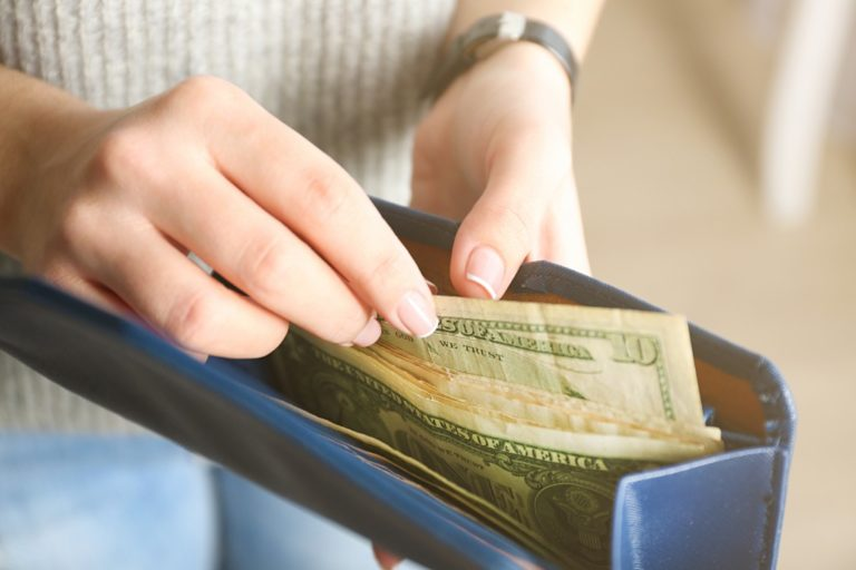 woman pulling cash out of wallet