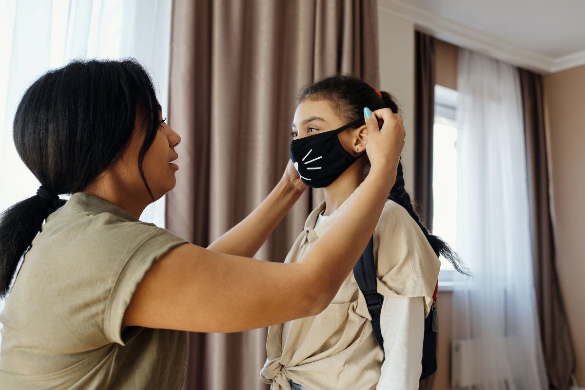 woman putting facemask on child