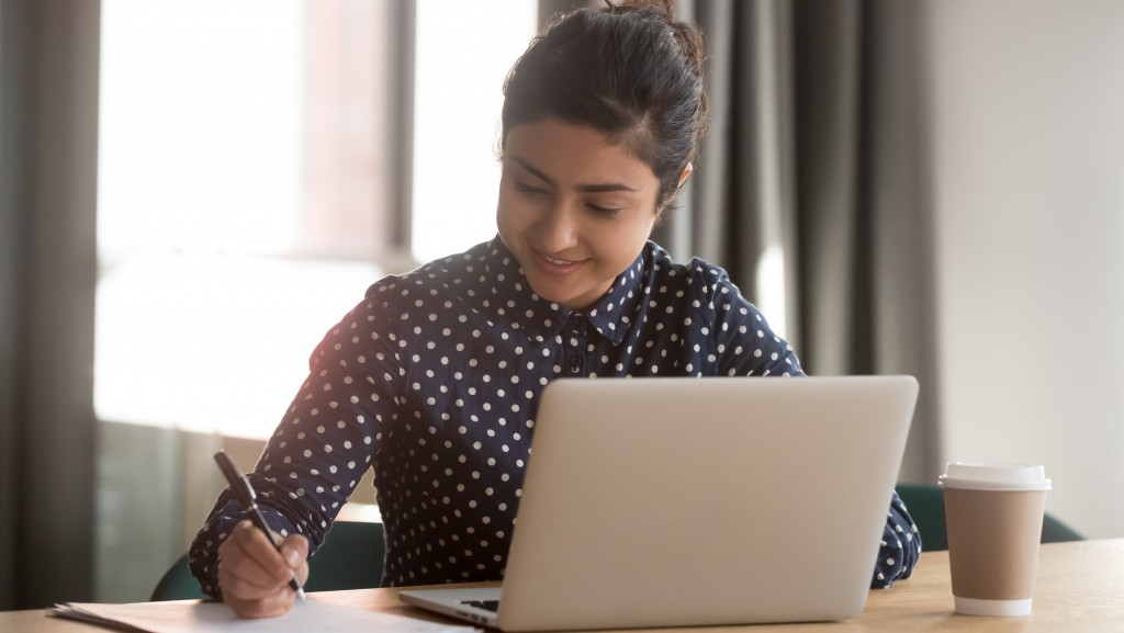 woman writing note working on laptop